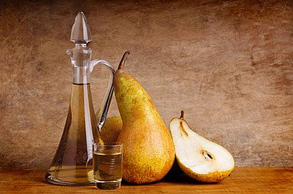 still life composition with traditional fruit brandy and pears on a vintage grunge wooden background