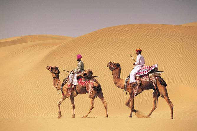 Two men on camelback in desert, Jaiselmer, India 546003